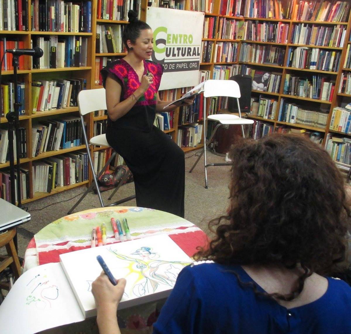 Andrea Tierra recita sus poemas, mientras Kinklo inspirada dibuja.